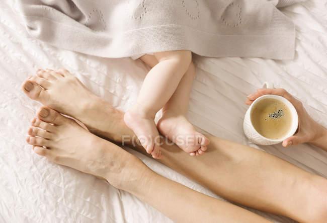 Mutter und Baby barfuß auf dem Bett — Stockfoto