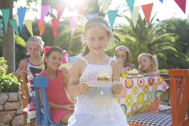 Meninas na festa de aniversário segurando prato com cupcake — Fotografia de Stock