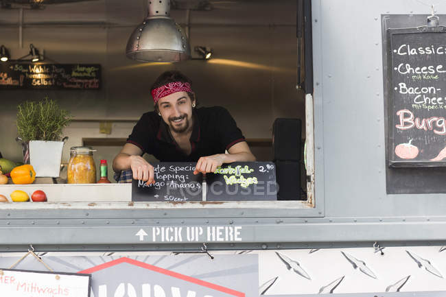 Portrait of young man at hatch of fast food van — стокове фото