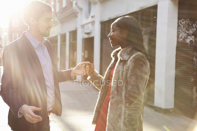 Casal de pé na rua, cara a cara, de mãos dadas — Fotografia de Stock