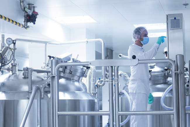 Worker operating pharmaceutical production equipment in pharmaceutical plant — Stock Photo