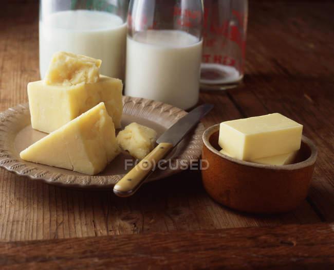Сыр, сливочное масло и молочные бутылки на деревянный стол — стоковое фото