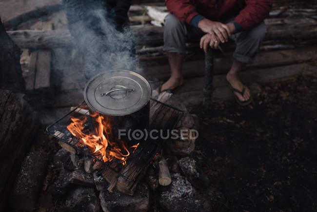 Senior homme assis sur un journal, je regarde pot de cuisson sur feu de camp, faible section — Photo de stock