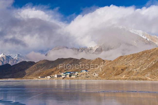 Berge und Dorf am See — Stockfoto