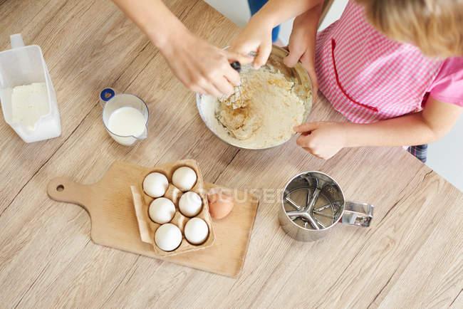 Mère aidant sa fille à fouetter les ingrédients ensemble dans un bol, vue aérienne — Photo de stock