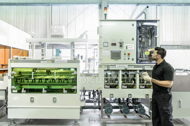 Worker with circuit board processing machine in electronics factory — Stock Photo