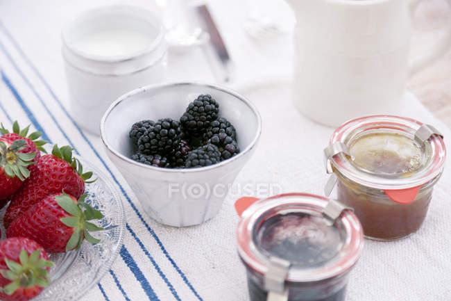 Frutta estiva in ciotole e conserva in vasetti sulla tovaglia — Foto stock