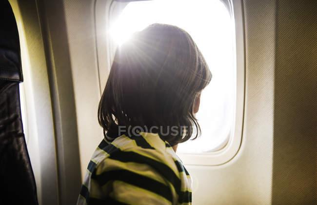 Menino no avião olhando através da janela do avião iluminado pelo sol — Fotografia de Stock