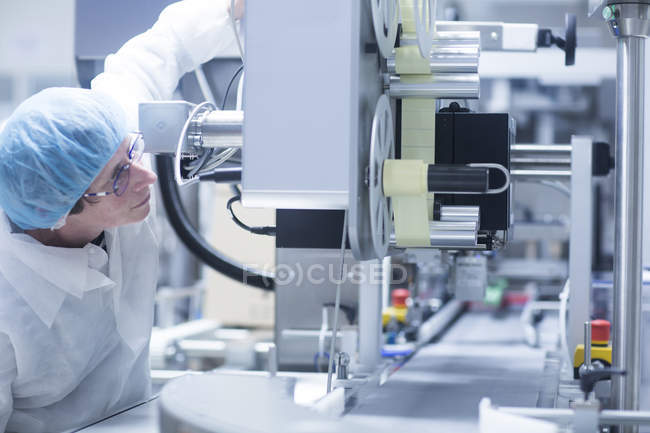 Worker operating machinery on production line in pharmaceutical plant — Stock Photo