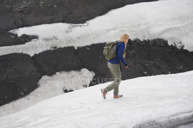 Hiker walking on snowy hillside — Stock Photo