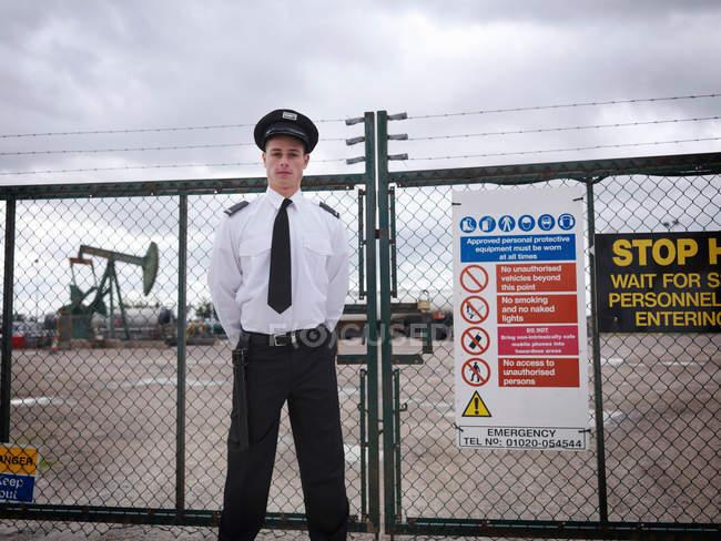 Gardien à la porte du puits de pétrole. En arrière-plan se trouve une pompe à huile au-dessus d'un puits de pétrole terrestre (hochant la tête âne / pompage ) — Photo de stock