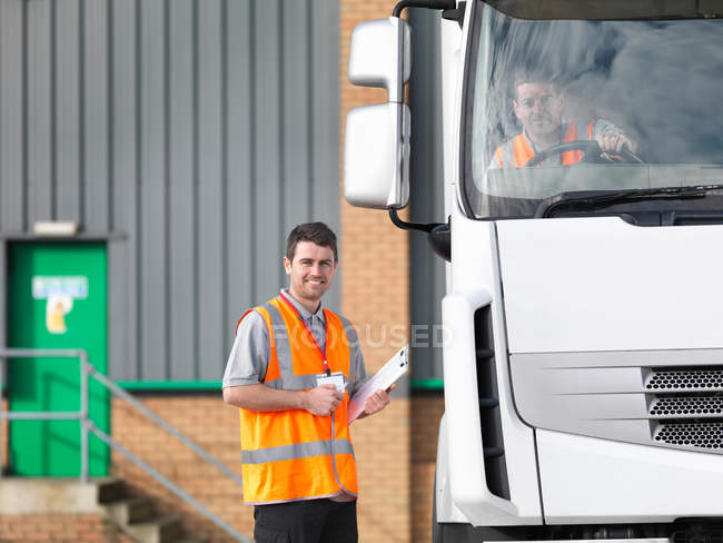 Inspector and truck driver in truck — Stock Photo