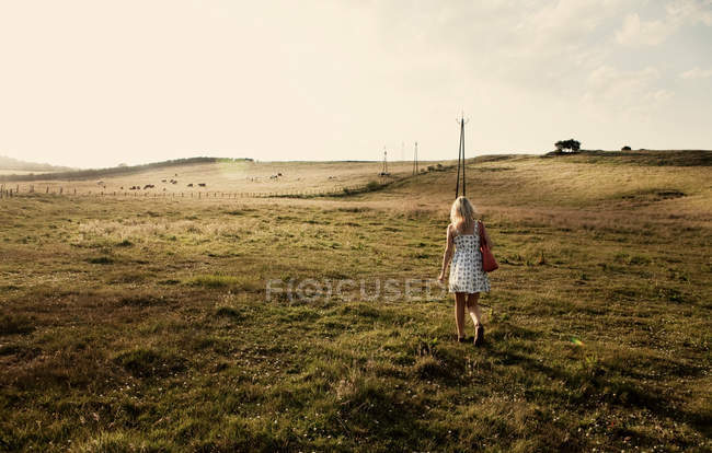 Young woman walking through field — Stock Photo