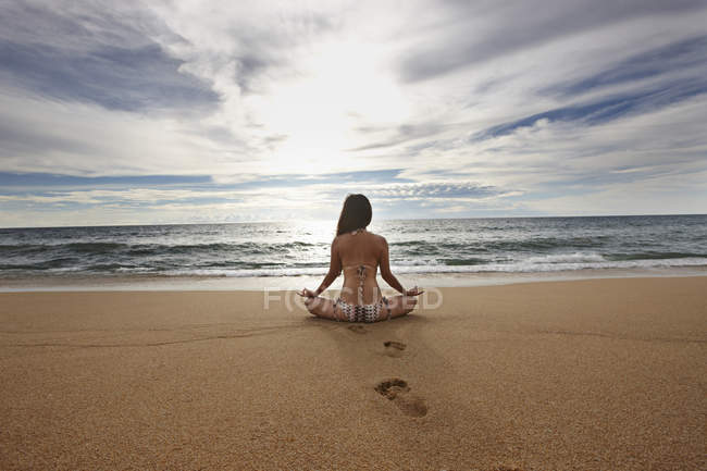 Woman meditating on sandy beach — Stock Photo