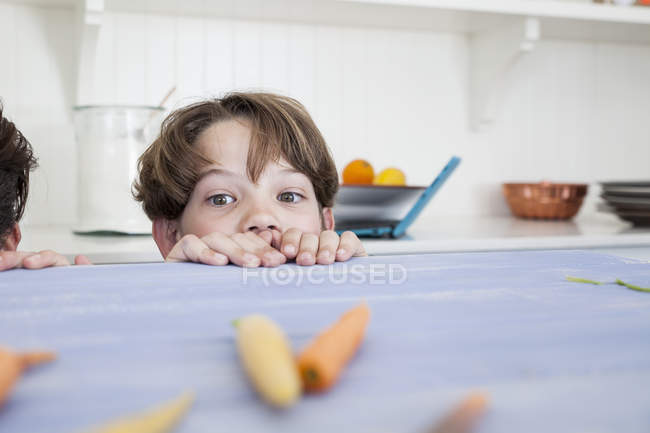 Young boy peering over kitchen work surface — Stock Photo