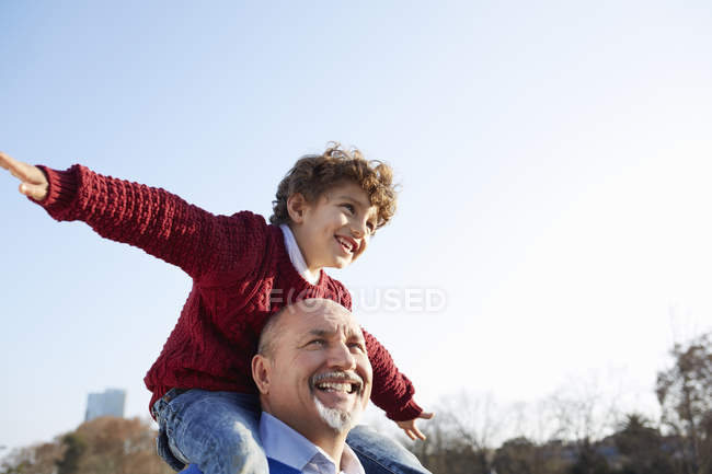 Grandson sitting on grandfathers shoulders, arms out smiling — Stock Photo