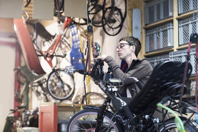 Жінка в майстерню з ремонту велосипедів ремонту лежачому велосипеді — стокове фото