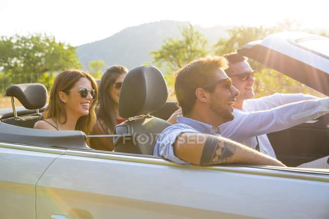 Чотири дорослих друзів водіння на сільській дорозі в конвертованій, Майорка, Іспанія — стокове фото