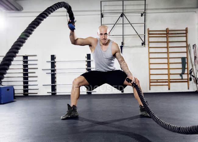 Середині дорослої людини за допомогою боротьбу мотузки в тренажерний зал — стокове фото