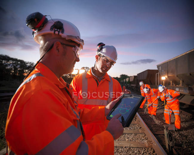 Railway workers using digital tablet to view work details on railway tracks — Stock Photo