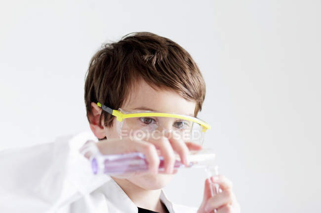 Student pouring liquid into test tubes — Stock Photo
