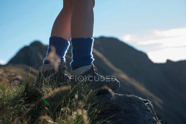 Jambes de femme de randonnée sur la colline rurale — Photo de stock