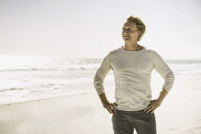 Mature man standing on beach, looking into distance — Stock Photo