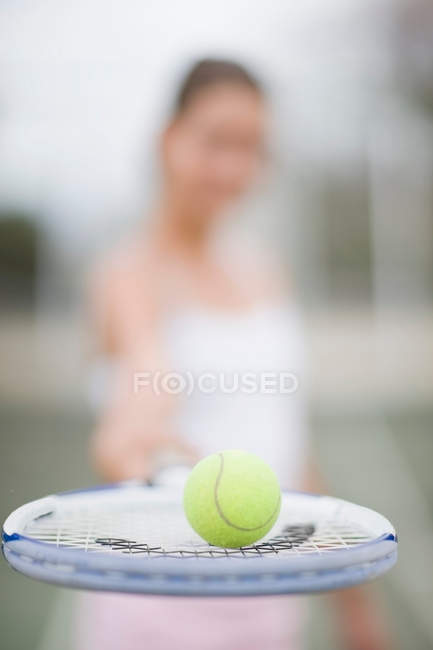 Tennis ball balanced on racket, close-up view, selective focus — Stock Photo
