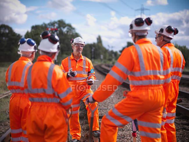 Foreman instructing railway workers on railway tracks — Stock Photo