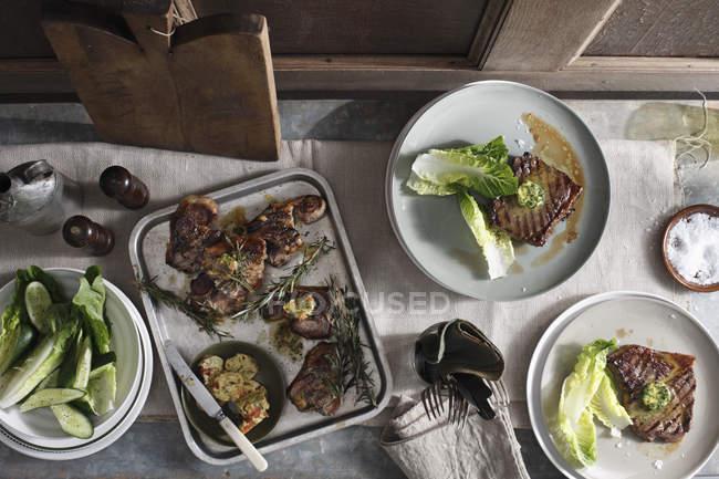 Порції стейки з листям салату, випічки лоток з вареного м'яса, чаша свіжих овочів на столі, Натюрморт — стокове фото