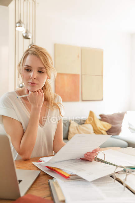 Woman working with paperwork and looking at laptop — Stock Photo
