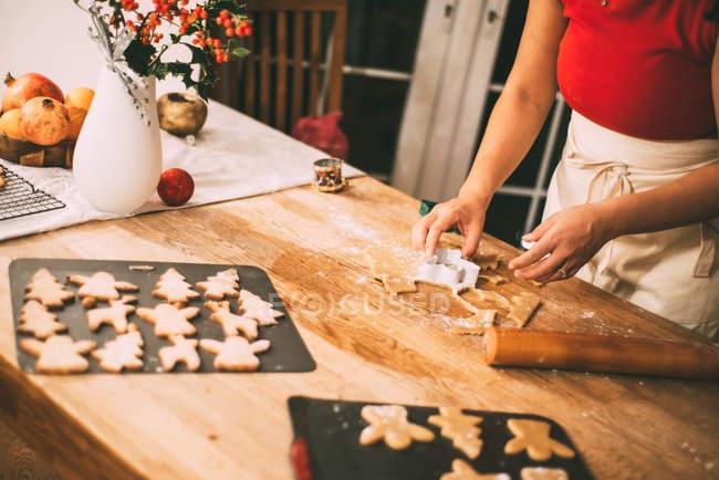 Image recadrée de femme coupe biscuits de Noël avec emporte-pièce au comptoir de la cuisine — Photo de stock
