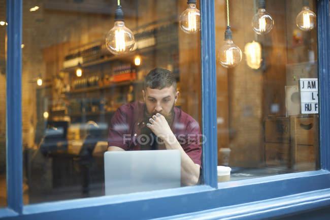 Vue de fenêtre de jeune homme utilisant l'ordinateur portatif dans le café — Photo de stock