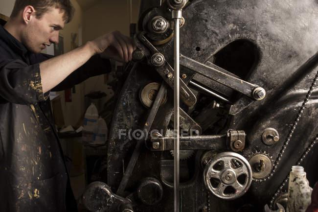Giovane stampante maschio che utilizza macchinari per la stampa in officina di stampa — Foto stock