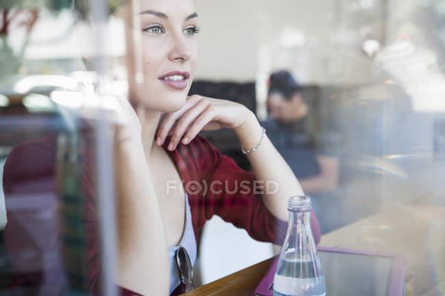 Giovane donna che si siede nel caffè, guardando fuori della finestra — Foto stock
