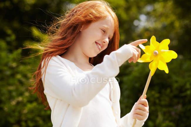 Girl playing with pinwheel outdoors — Stock Photo