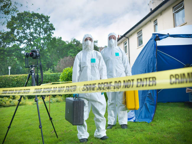 Forensic scientists behind police tape at crime scene — Stock Photo