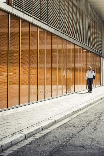 Бізнесмен, йдучи за межі офісної будівлі біля стіни — стокове фото