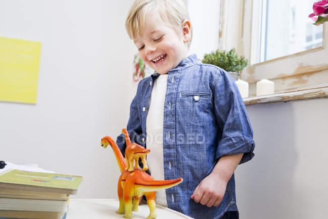 Menino brincando com os dinossauros de brinquedo em casa — Fotografia de Stock