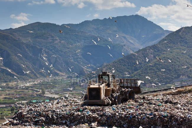 Máquinas trabalhando sobre os resíduos em aterro sanitário — Fotografia de Stock