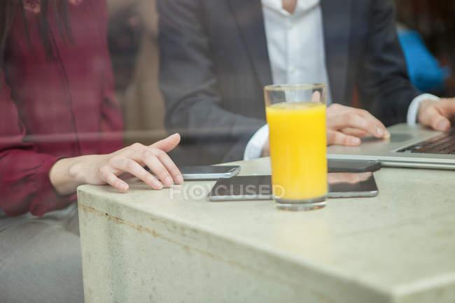 Femme d'affaires et homme d'affaires travaillant avec ordinateur portable au café — Photo de stock