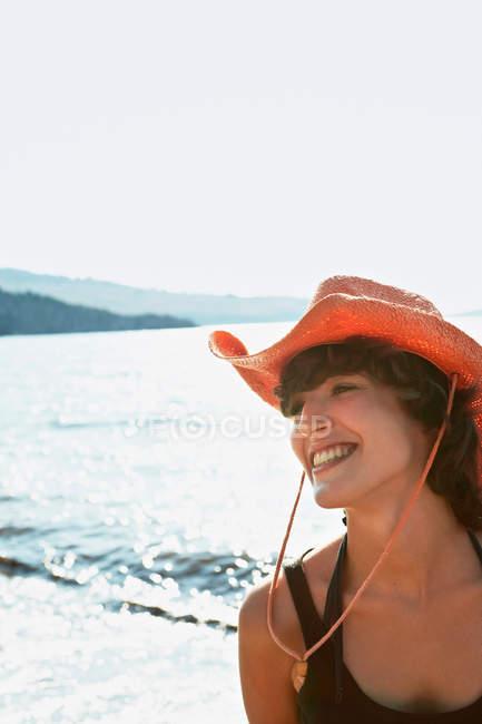 Lächelnde Frau mit Sonnenhut am Strand — Stockfoto