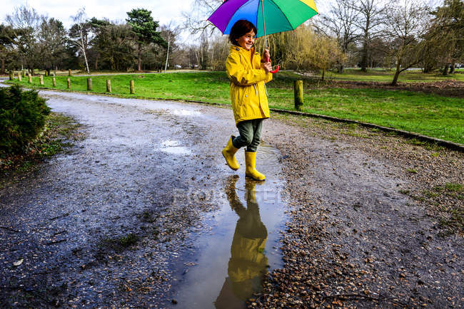 Boy in yellow anorak carrying umbrella in park — Stock Photo
