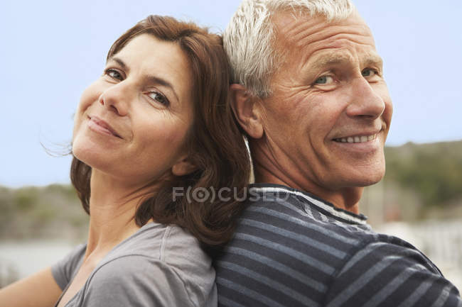 Middle aged couple, back to back, smiles — Stock Photo