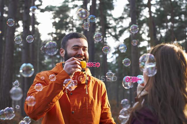 Pareja joven soplando burbujas en el bosque - foto de stock