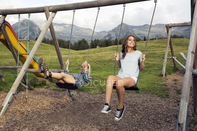 Дві жінки дорослих друзів, граючи на гойдалок в австрійських Альпах, Sattelbergalm, Тіроль, Австрія — стокове фото