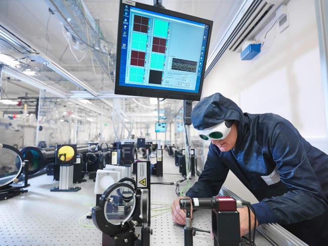 Male scientist in protective clothing and goggles setting up laser path in laboratory — Stock Photo