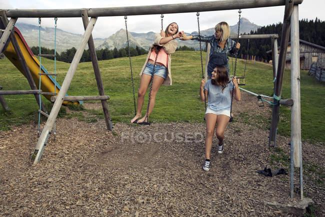 Троє дорослих друзів, які грають на гойдалок в австрійських Альпах, Sattelbergalm, Тіроль, Австрія — стокове фото