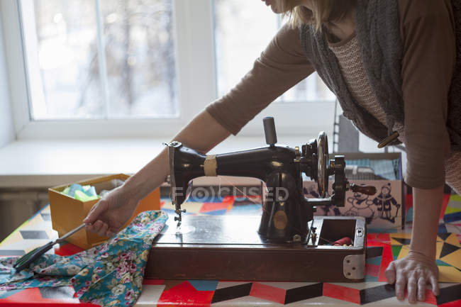 Woman with vintage sewing machine reaching for scissors at table — Stock Photo