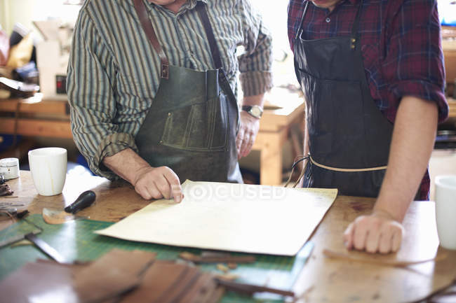 Two male workers in leather workshop, looking at plans, mid section — Stock Photo